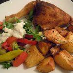 Brathähnchenschenkel mit buntem Salat und Kartoffelspalten