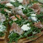 Pizza mit Parmaschinken. Rucola und Parmesan