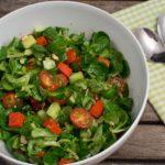 Grüner Salat mit rotem Pestokäse und Nüssen