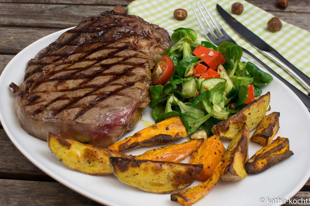 Steak mit zweierlei Kartoffelspalten und Salat mit Pestokäse und Walnüssen