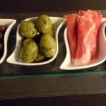 Tapas – verschiedene Oliven und Seranoschinken-Röllchen
