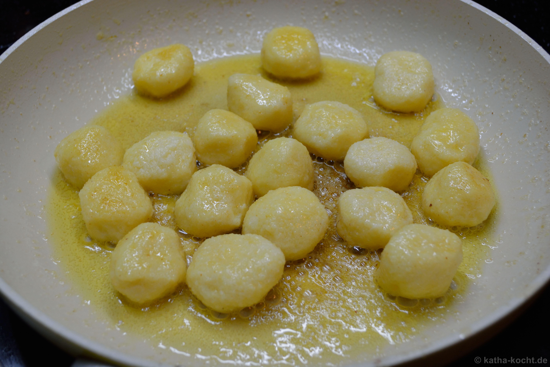 Die Gnudi mit einigen frittierten Salbeiblättern auf Tellern ...